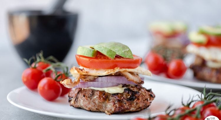 chicken burgers topped with bacon, tomato, onion, egg, avocado