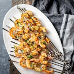 Platter with skewers of herbed grilled shrimp