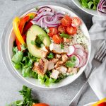 Low carb chipotle chicken burrito bowl surrounded by fresh produce