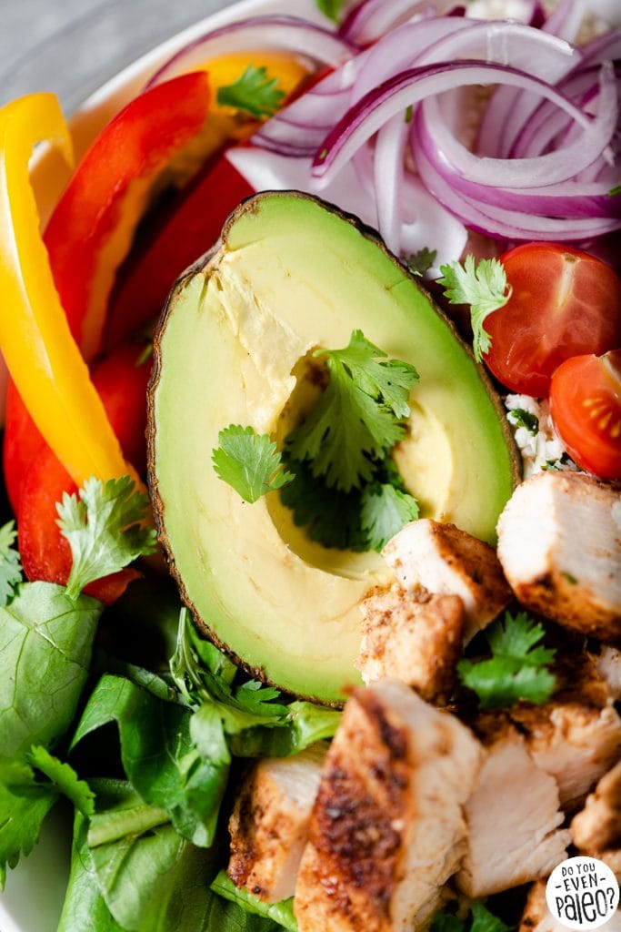 Closeup of an avocado on a bed of fresh veggies