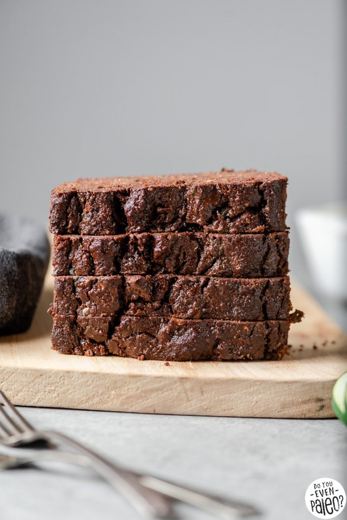 Slices of gluten free chocolate zucchini bread stacked on a cutting board