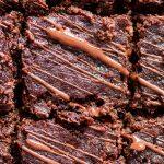 Closeup of paleo zucchini brownies, drizzled in chocolate