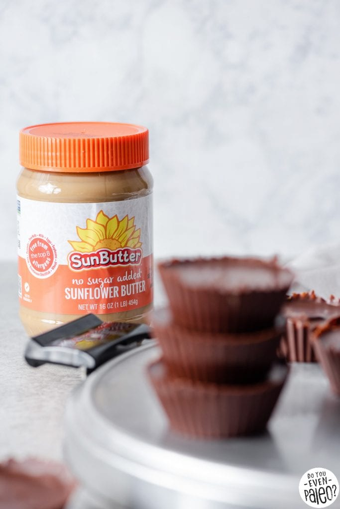 Jar of SunButter sunflower seed butter with chocolate cups stacked in the forefront
