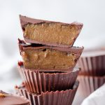 Closeup view of homemade sunflower seed butter cups, one sliced in half