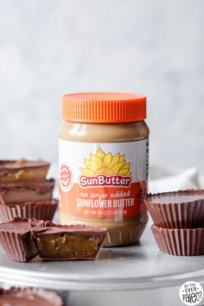 A jar of SunButter cups surrounded by homemade pumpkin spice chocolate cups