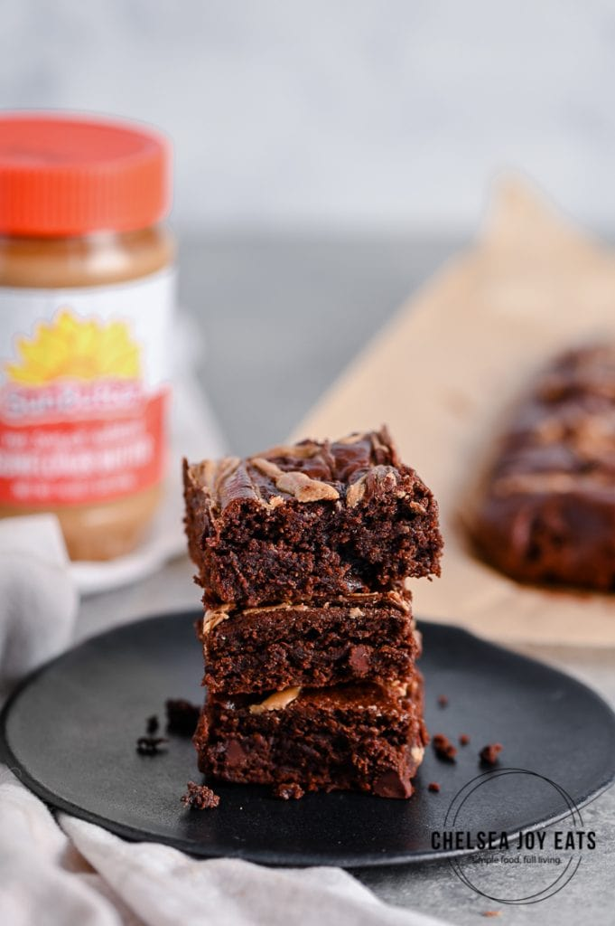 Stack of paleo brownies with a jar of SunButter in the background