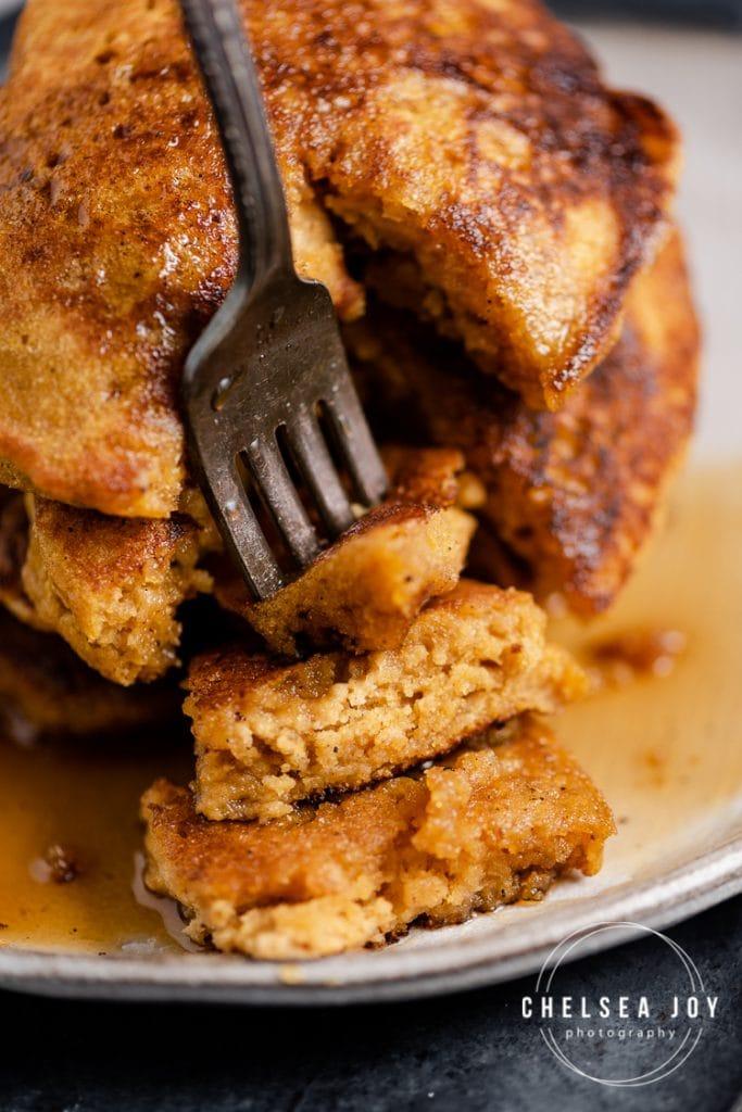 Closeup of a fork piercing a section of gluten free pumpkin pancakes