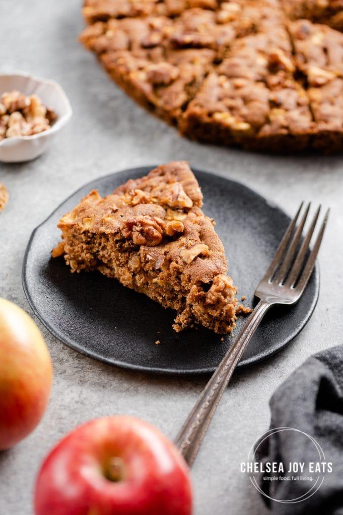 Slice of gluten free apple snack cake on a black plate