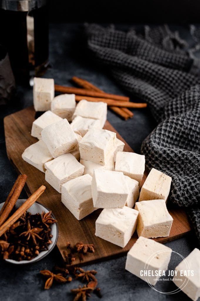 Homemade marshmallows scattered across a wooden board