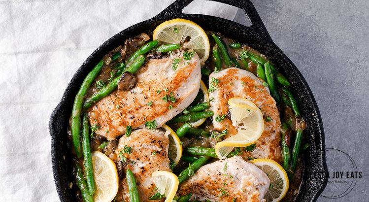 Chicken, green beans, and lemon slices in a cast iron skillet