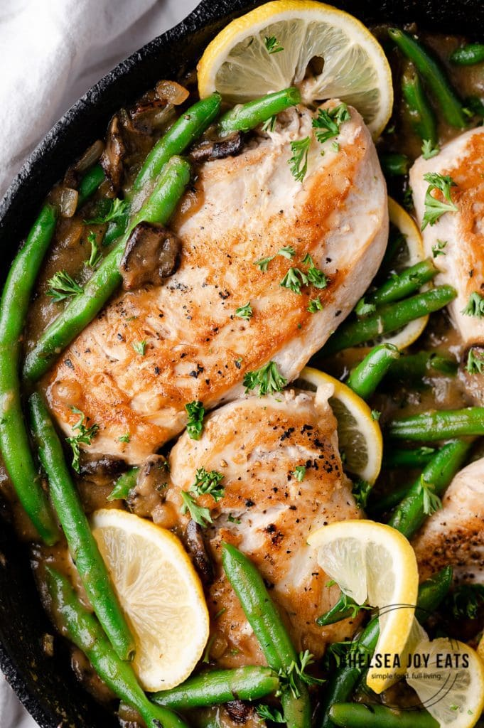 Closeup of chicken breasts in a skillet with green beans and mushroom sauce