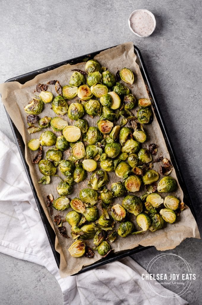 Baking sheet of roasted brussels sprouts on a concrete background