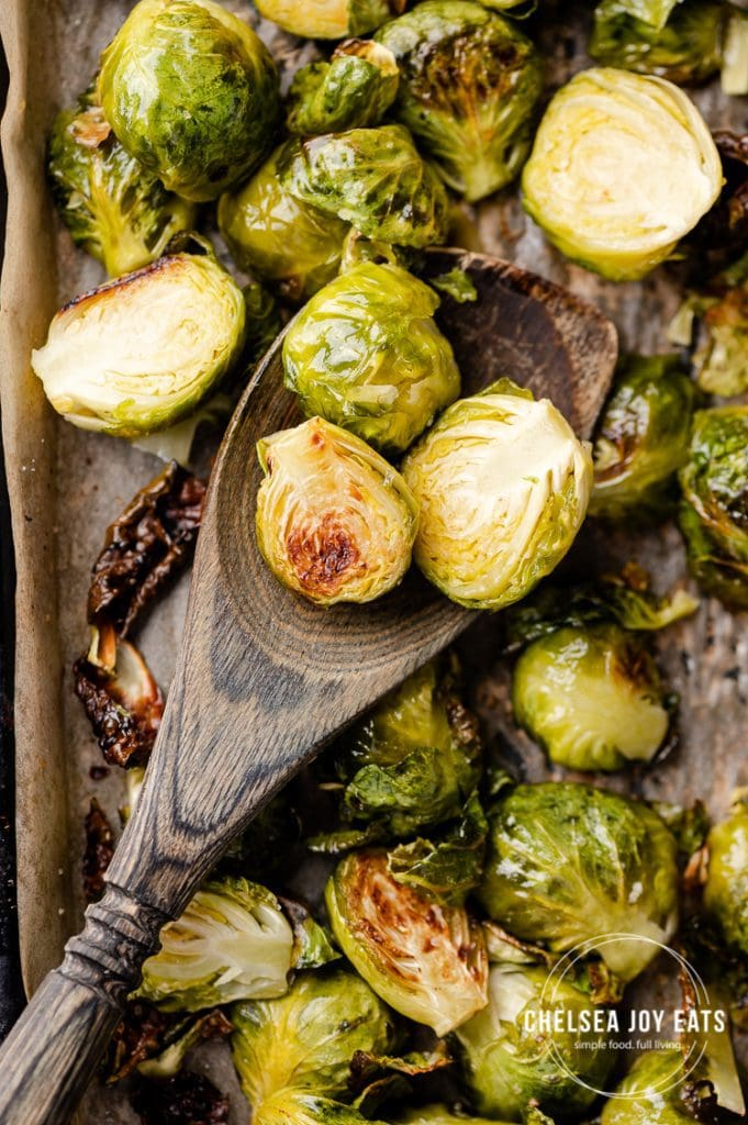 Closeup of brussels sprouts being stirred by a wooden spatula