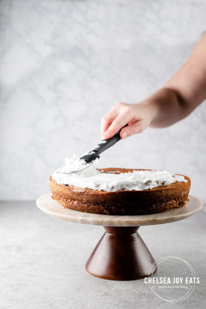Woman frosting a plantain cake with coconut whipped cream