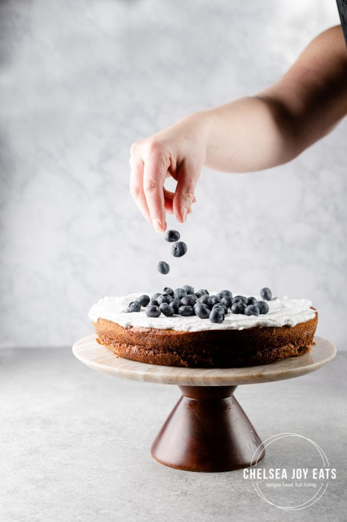 Woman decorating a sweet plantain cake with blueberries