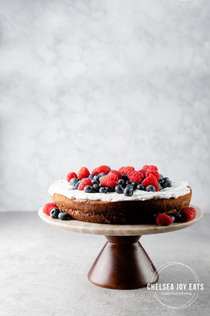 Flourless sweet plantain cake frosted with coconut whipping cream and fresh berries