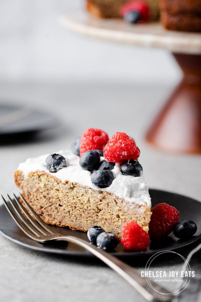 Closeup of a piece of plantain cake topped with coconut whipped cream and berries
