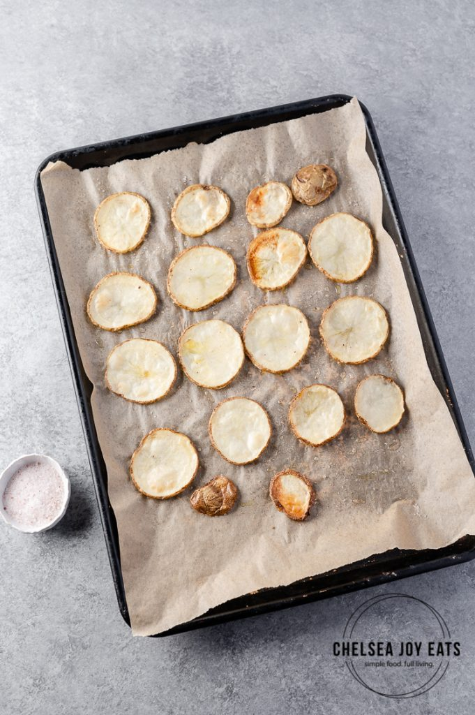 Tray of roasted potato rounds with a dish of sea salt