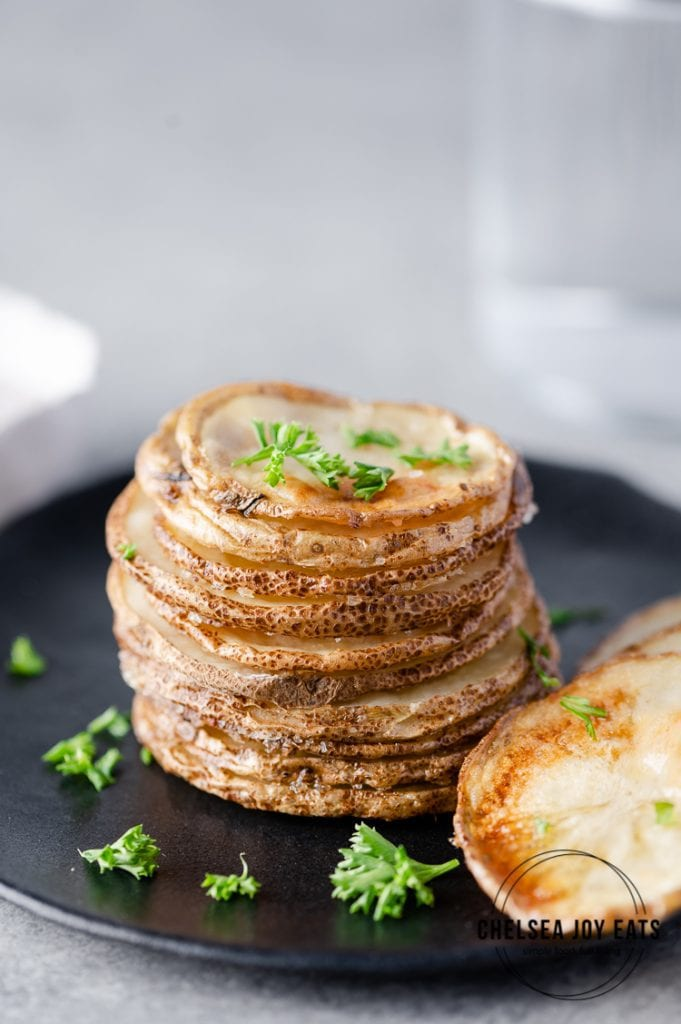 Stack of roasted potato slices garnished with parsley