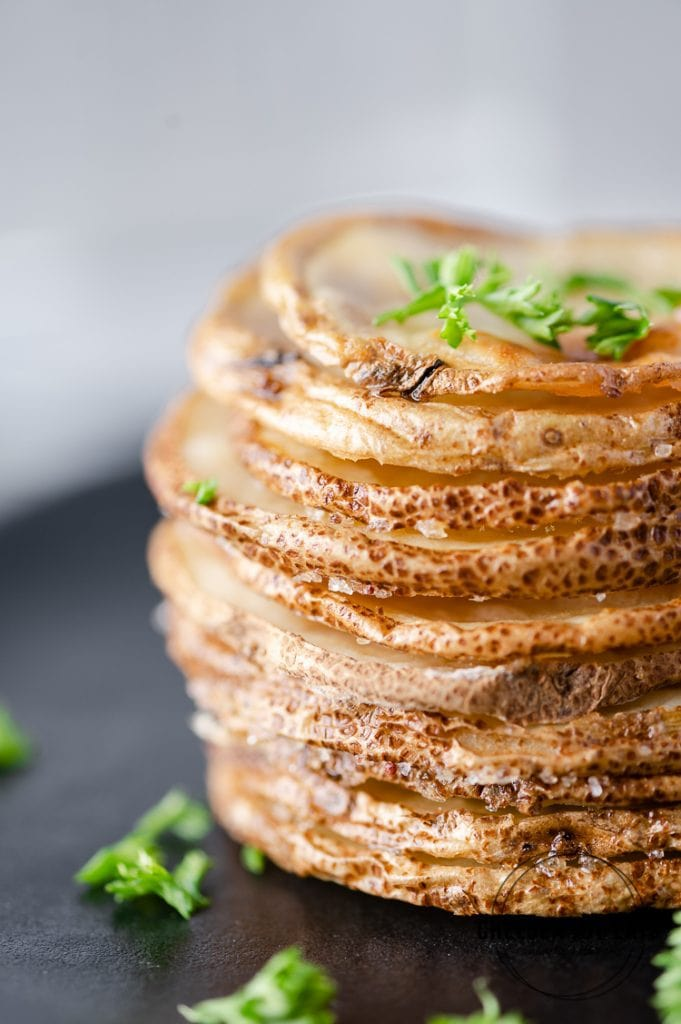 Closeup of a stack of roasted potato slices garnished with parsley