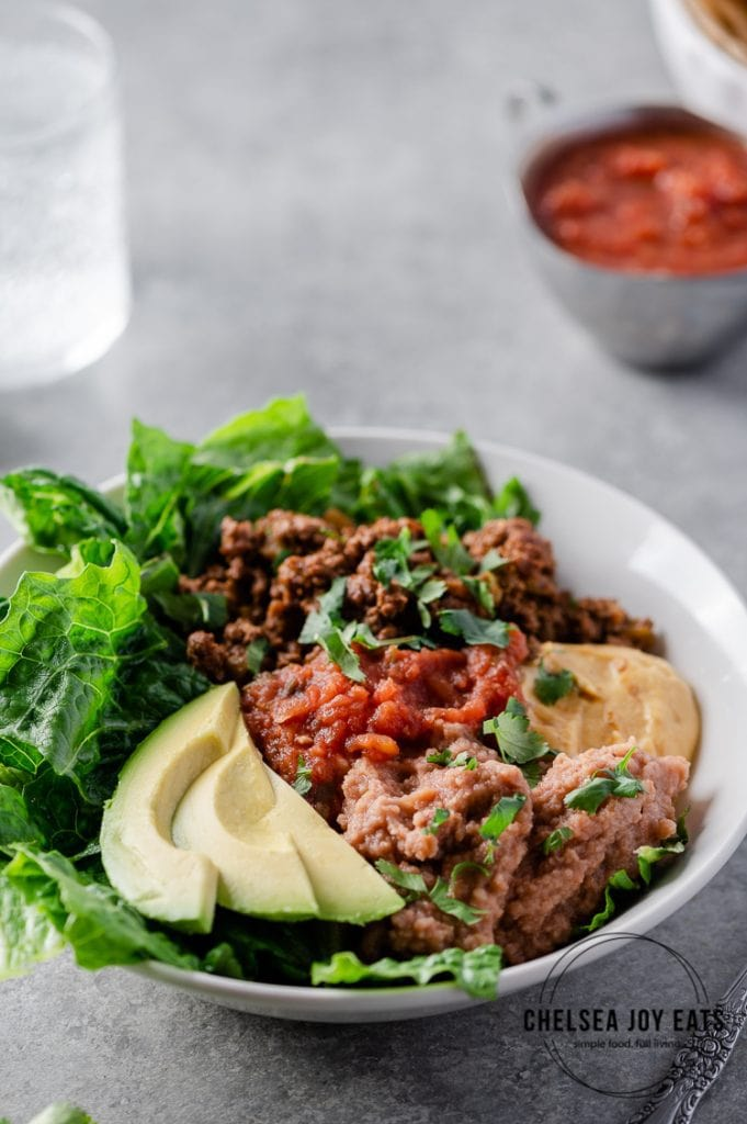 Closeup of a taco salad bowl with avocado, taco meat, lettuce, refried beans, and dairy free cheese sauce