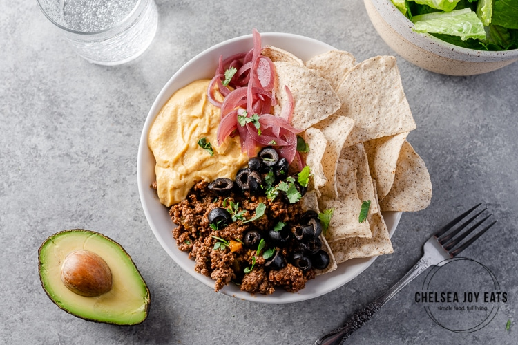 Taco bowl recipe with grain free chips, taco meat, black olives, dairy free cheese sauce, and pickled red onions